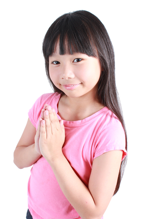 greet eyes: Young asian girl put her hands together and pray over white background. Stock Photo