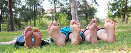 children background: Group of happy children lying on green grass outdoors in spring park