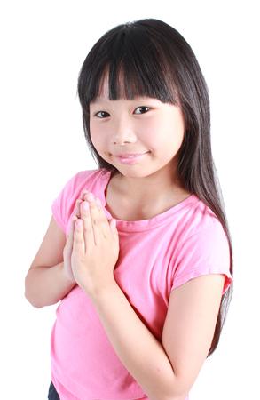 respetar: Muchacha asiática joven juntó las manos y rezar Foto de archivo
