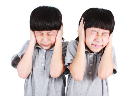 Asian twins boys cover their ears isolated on white background