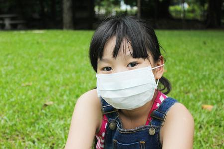 Meisje heeft koorts en draag beschermingsmasker met groene grasachtergrond. Stockfoto