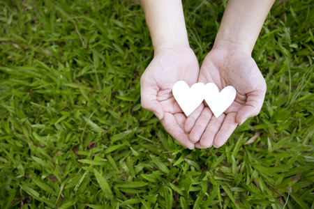Two hands holding two white hearts on green grass background.