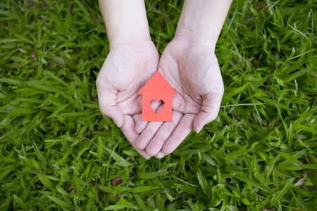 heart in hand: hands holding red paper house over green grass. Stock Photo