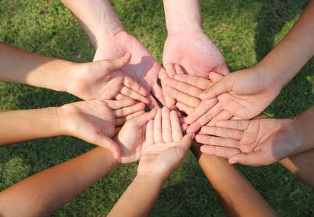 Multicultural hands, children hands on grass background.