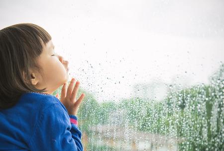 Meisje kijkt uit het raam met groen boszicht.