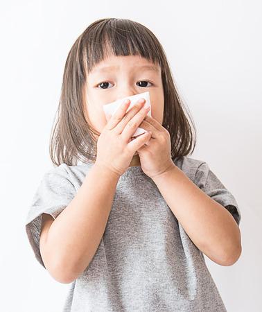 Leuk klein Aziatisch meisje blaast haar neus over witte achtergrond (Aziatisch)