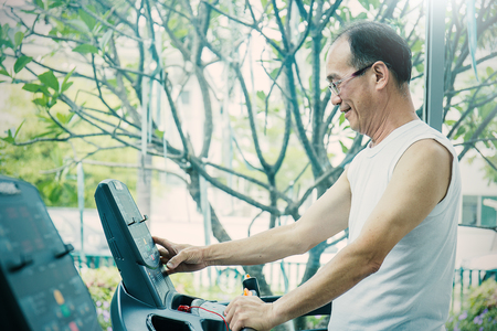 Asian senior man pushing the button and running on a treadmill, close up with copy space Stock Photo - 83058161