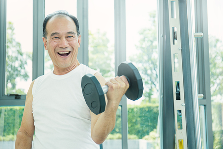 Asian senior male doing weight training with dumbbells Stockfoto
