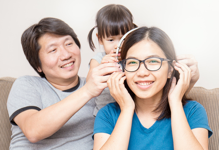 couch: Asian parents and baby girl in sofa using tablet and headphones