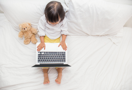 Top view of cute young girl using laptop with copy space .