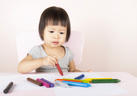 litle: Adorable child drawing with colorful crayons and smiling, with the copy space