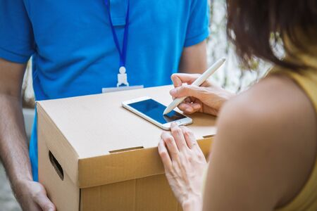 Woman appending signature after accepting a delivery of boxes from deliveryman Stock Photo