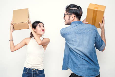 Man and woman fighting with boxes. Young Asian small business owner SME man and woman at home office, online marketing packaging and delivery, SME concept