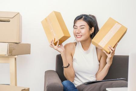 Poner en marcha un empresario de pequeña empresa o una mujer independiente que tenga cajas trabajando en el concepto de casa, propietario de una pequeña empresa asiática joven en la oficina de la casa, marketing en línea empaquetado y entrega