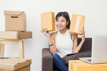 Start up small business entrepreneur or freelance woman holding boxes working at home concept, Young Asian small business owner at home office, on line marketing packaging and delivery Stock Photo
