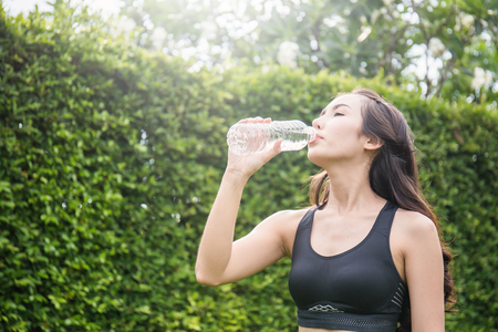 Asian young woman drinking water after sport over green leaves background