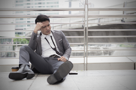 Stressed asian businessman bankrupt with sitting at outdoor. Banco de Imagens - 87632483