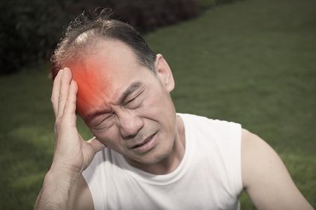 頭を抱えているストレス男性。自然の背景にシニア男性。悲しみと痛み