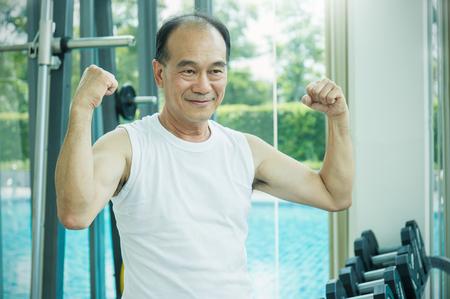 levantar peso: Hombre senior asiático haciendo entrenamiento con pesas, hombre senior feliz mostrando su bíceps en el gimnasio (tío, abuelo, viejo) Foto de archivo