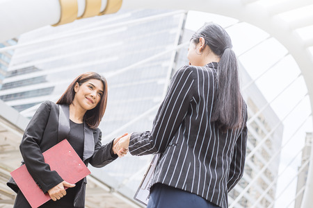 Business concept. Two young beautiful business women shaking hands in street outdoors Stock Photo