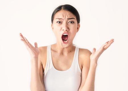 Porträt der verärgerten nachdenklichen wütenden verrückten Frau, die heraus schreien (Ausdruck, Gesichtsbehandlung), Schönheitsportrait der jungen asiatischen Frau getrennt auf weißem Hintergrund. Standard-Bild