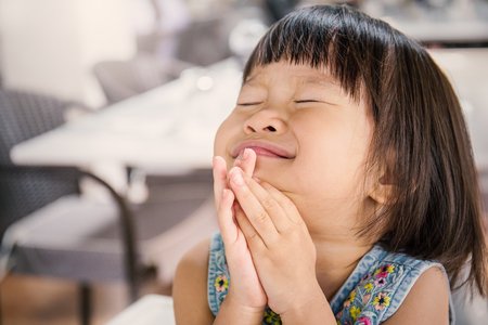Portrait of little cute asian girl praying, close up expression
