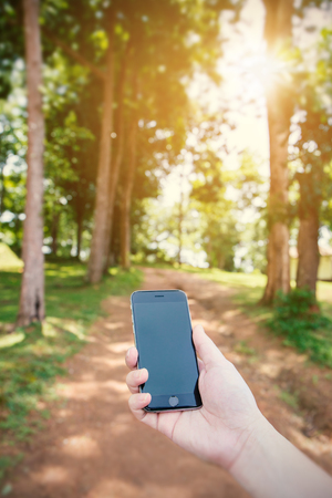 travel concept, hand holding smart phone in nature background, outdoor activity