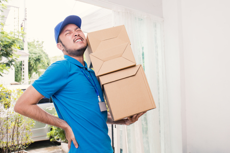 Portrait of delivery asian man with hands holding cardboard box, asian delivery man having back pain during delivery boxes. Foto de archivo