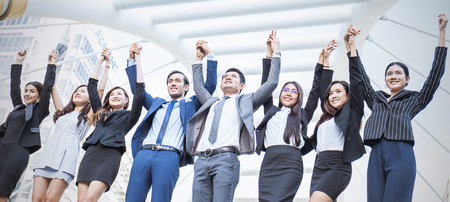 Portrait of confident business people group standing in row and with their hands holding and rise up, teamwork multicultural and togetherness concept, asian business man and woman stant in line outdoors.