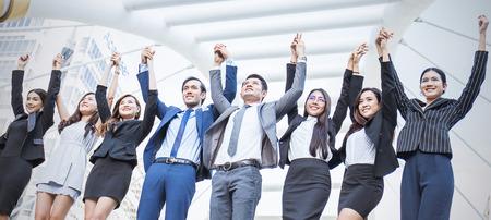 Portret van zekere bedrijfsmensengroep die zich in rij en met hun handen bevinden en omhooggaand, groepswerkmulticultureel en samenhorigheidsconcept, Aziatische bedrijfsman en vrouwen stant in lijn in openlucht bevinden zich.