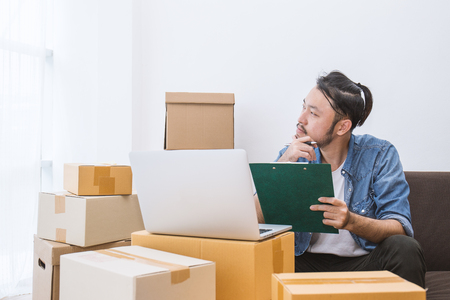 Start up small business entrepreneur SME or freelance man working at home concept, Portrait of young Asian small business owner at home office, online marketing packaging and delivery, SME concept 스톡 콘텐츠