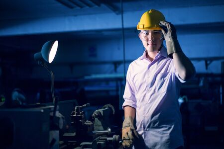 Portrait of young adult experienced industrial asian worker over industry machinery production line manufacturing workshop Stock Photo