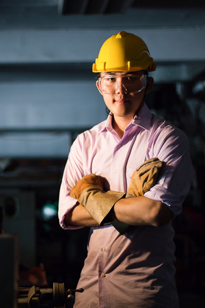 assembler: Portrait of young adult experienced industrial asian worker over industry machinery production line manufacturing workshop Stock Photo