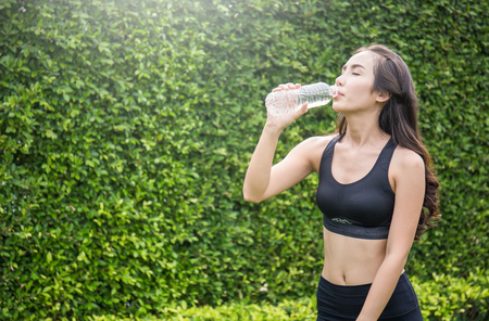 Asian young woman drinking water after exercise, asian athlete drinking a bottle of water over green leaves garden background Stock Photo