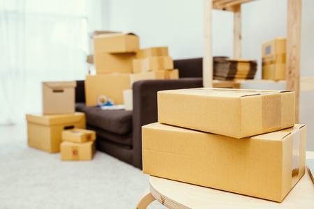 Regeling van lege kartonverpakkingsdozen die zich op een vloer met exemplaarruimte bevinden, KMO-levering, bewegend huisconcept
