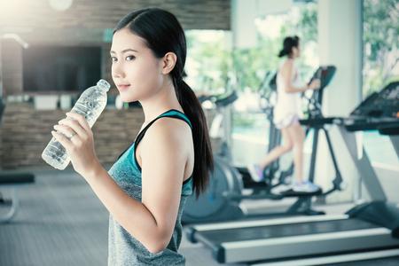 아시아 젊은 여자가 마시는 물 스포츠 클럽, 체육관에서 물 한 병 마시는 아시아 선수. 스포츠 및 건강 관리 개념