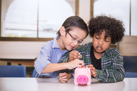 Two Little boys putting money into piggy bank for future savings, multicultural together eduaction concept