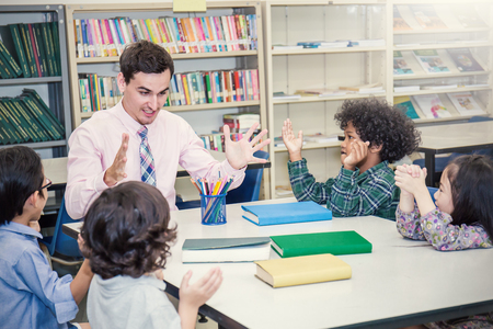 Pupils studying with teacher at desks in classroom,  Teacher and little children sitting discuss about lesson. Young students study in the classroom. Home school back to school concept. Stok Fotoğraf - 87938700