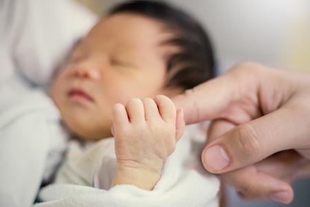 Aziatische pasgeboren de vadervinger van de babyholding, Close-uphand van Aziatische pasgeboren baby Stockfoto