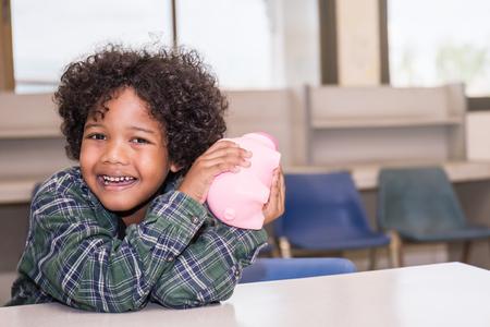 ittle: Little boys putting money into piggy bank for future savings