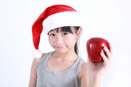 Portrait of little cute asian girl wearing red hat holding red apple