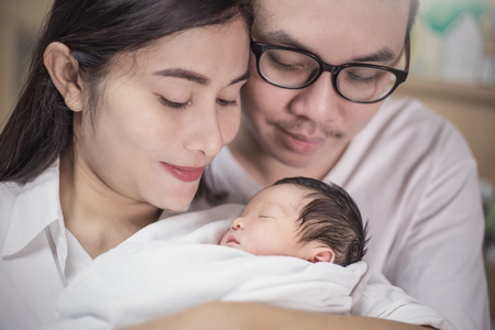 Padres asiáticos con bebé recién nacido, cerca retrato de joven pareja asiática con su bebé recién nacido.
