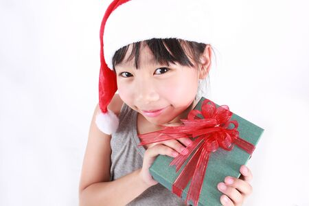 Portrait of little cute asian girl wearing red hat holding boxes of gift, christmas boxing day concept