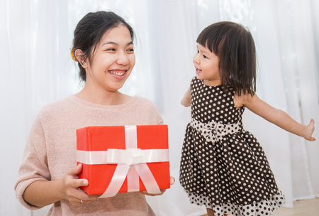 Little asian girl surprise her mother with gift box. Boxing day holiday birthday christmas and mother's day concept.