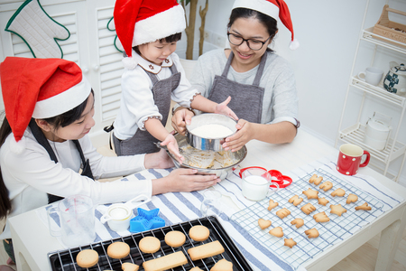Little asian girl with her sister and mother baking cake and cookies in the kitchen christmas eve holiday celebration. Happy asian family Stock Photo