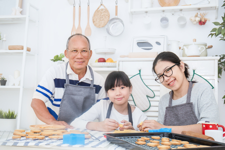 Portrait of little asian girl with her grandfather and her mother baking cake and cookies in the kitchen. Happy asian family and mother's day concept Banco de Imagens