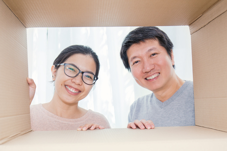 Asian couple man and woman looking into a cardboard box, Asian man and woman open the cardboard box with surprise expression on their face.