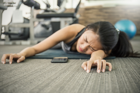 Asian tan woman fainting to the floor during her exercise at the sport club gym.