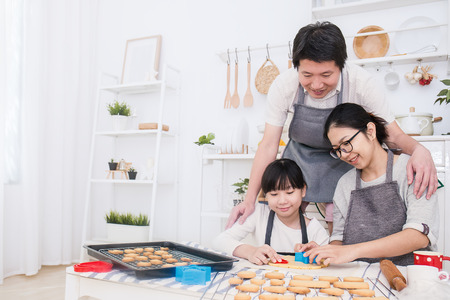 Portrait of little asian girl and her parents baking cake and cookies in the kitchen. Happy asian family and mother's day concept