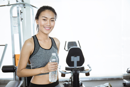 Asian young tan woman drinking water after exercise, asian athlete drinking a bottle of water at the sport club gym.